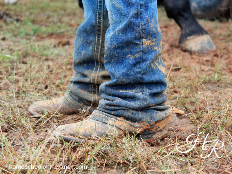 Child with muddy boots standing in straw while using rodeo as a homeschool elective