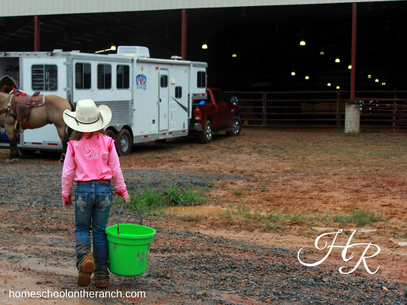 Child carrying bucket to horse trailer while using rodeo as a homeschool elective