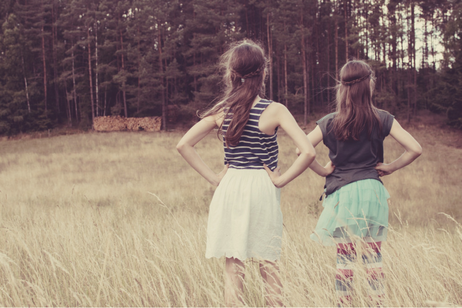 Two girls stand in a field while the wind blows through their hair.