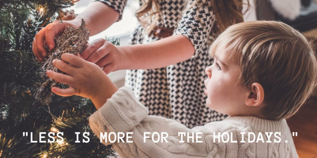 Small children decorate a simple tree with quote that states less is more for the holidays.