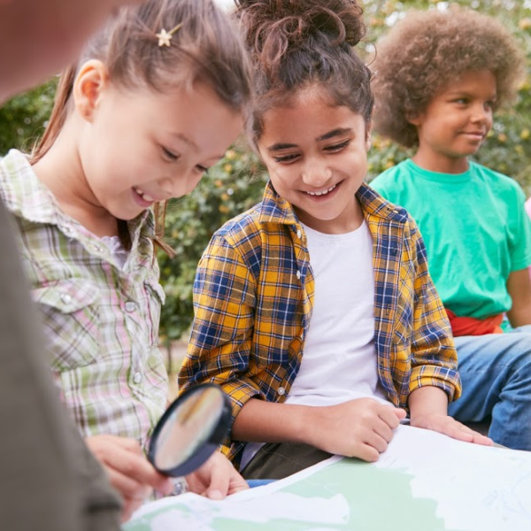 Homeschooled children On Outdoor Activity Camping Trip Looking At Map Together