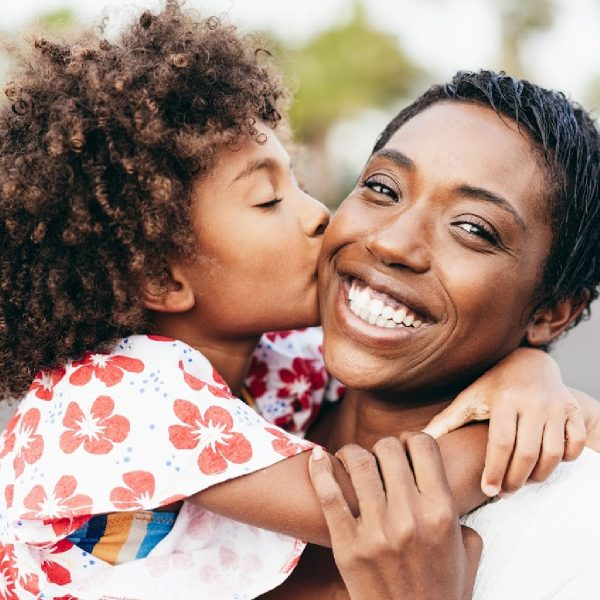 Happy young mother having fun with her child in summer day - Daughter kissing her mum outdoor - Family lifestyle, motherhood, love and tender moments concept - Focus on woman face