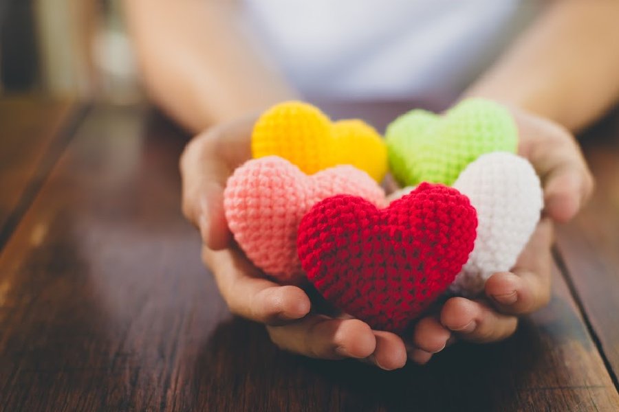 Mixed colors yarn heart on giving hands. Close up of colorful handmade. Healthy heart donation and health care concept. Valentine romance love forever theme