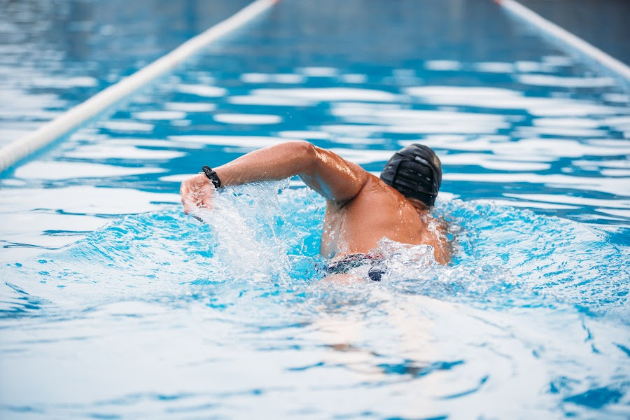 Athletic Young man swimming the back crawl in a pool. Swimming competition.
