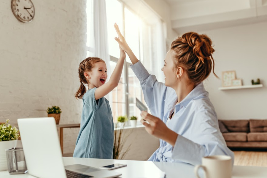 Low angle of excited small daughter giving high five to mother and screaming while celebrating successful online shopping using laptop at table in light living room
